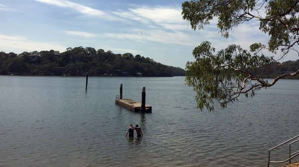 Two boys standing in the water in the Georges River about to swim