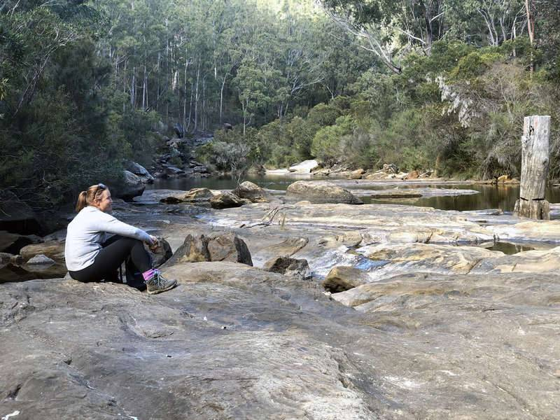 Female bushwalker sits admiring the Georges River at Freres Crossing, Campbelltown