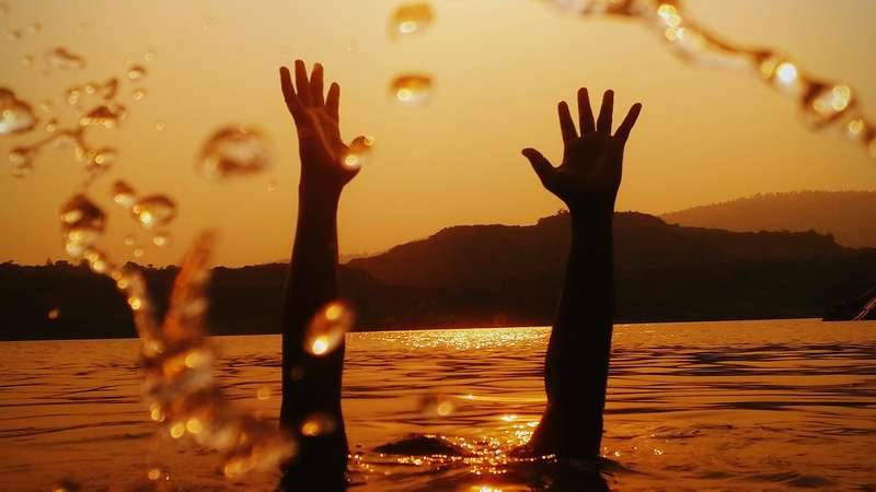 Person under water reaching hands up out of the water into the air, at sunset